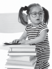young girl with glasses next to a pile of books