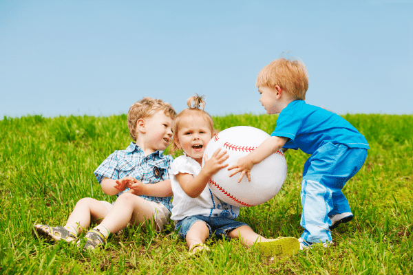 three young children playing in grass with ball