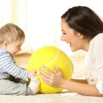 mom and child playing with large ball toy