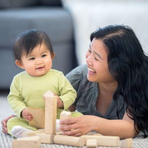 mom and child playing with blocks and smiling