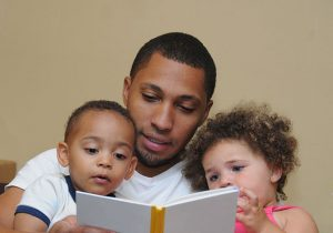 father reading to boy and girl
