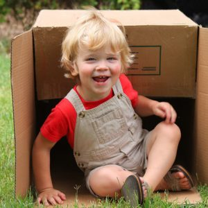 boy playing outdoors with box