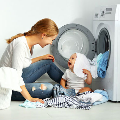 mom and child removing clothes from dryer