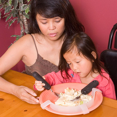 mom with daughter who is eating food from plate