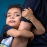 child clinging to parent's arm