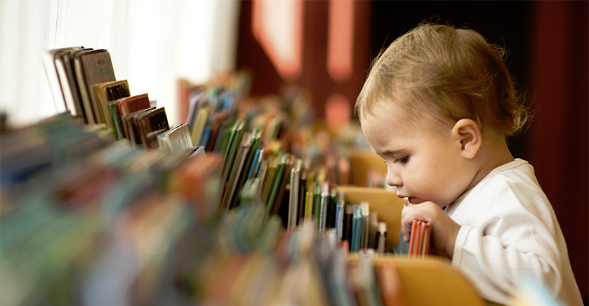 toddler looking at books in a library