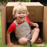 child sitting inside overturned box