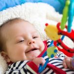 baby in crib with toy