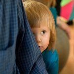child hiding behind parent
