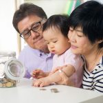 parents and child with jar of change
