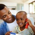 father holds son as he pretends to talk on toy phone